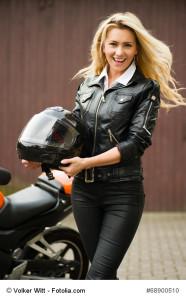 Motorradversicherung Ratgeber - Lachende junge Frau mit Motorradhelm
